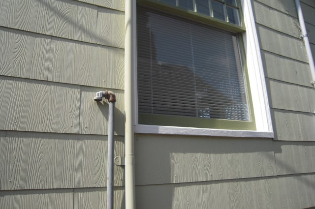 shows an underground oil tank breather tube on the outside of a house
