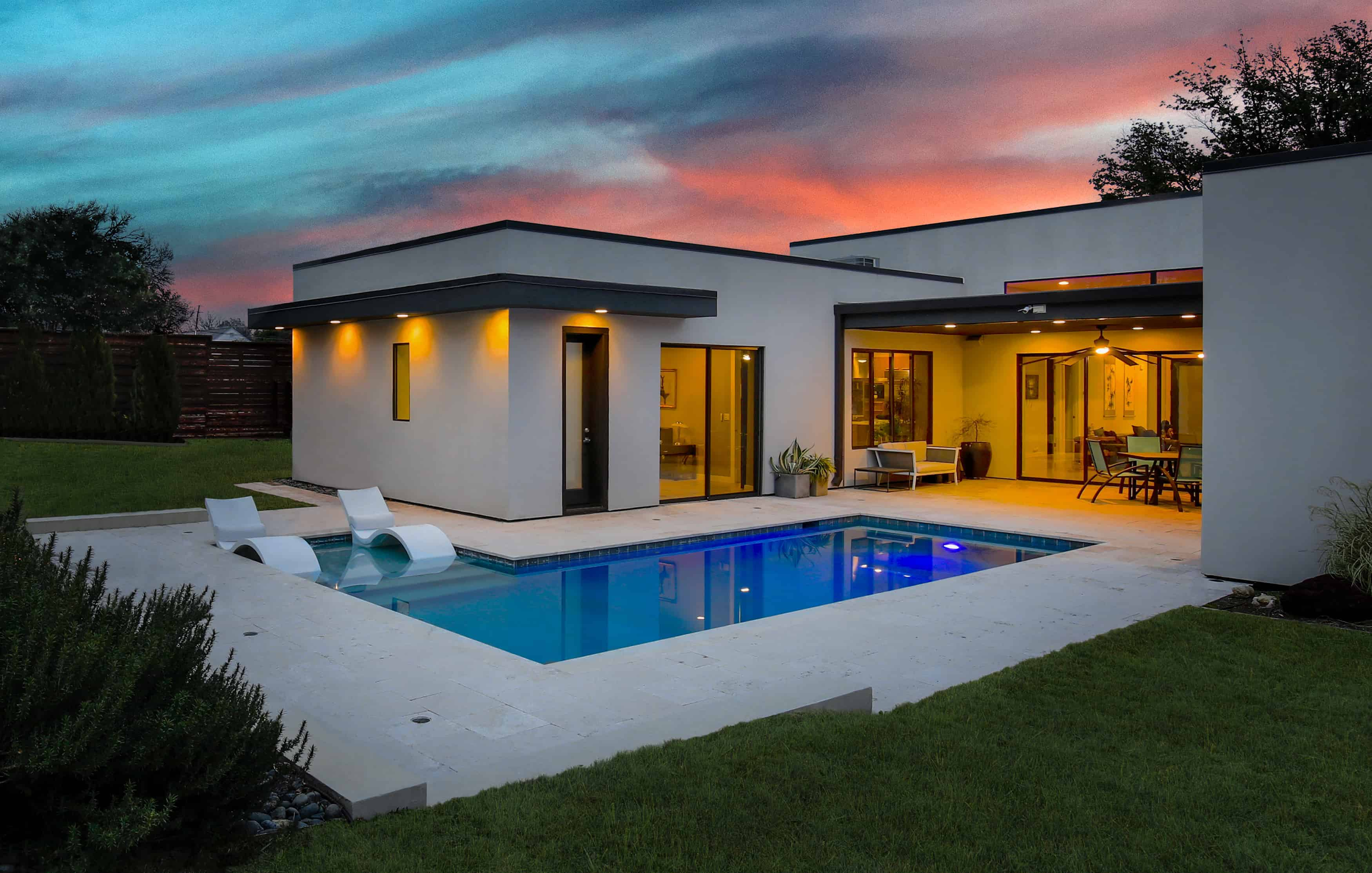 Modern home exterior with backyard pool and open concept