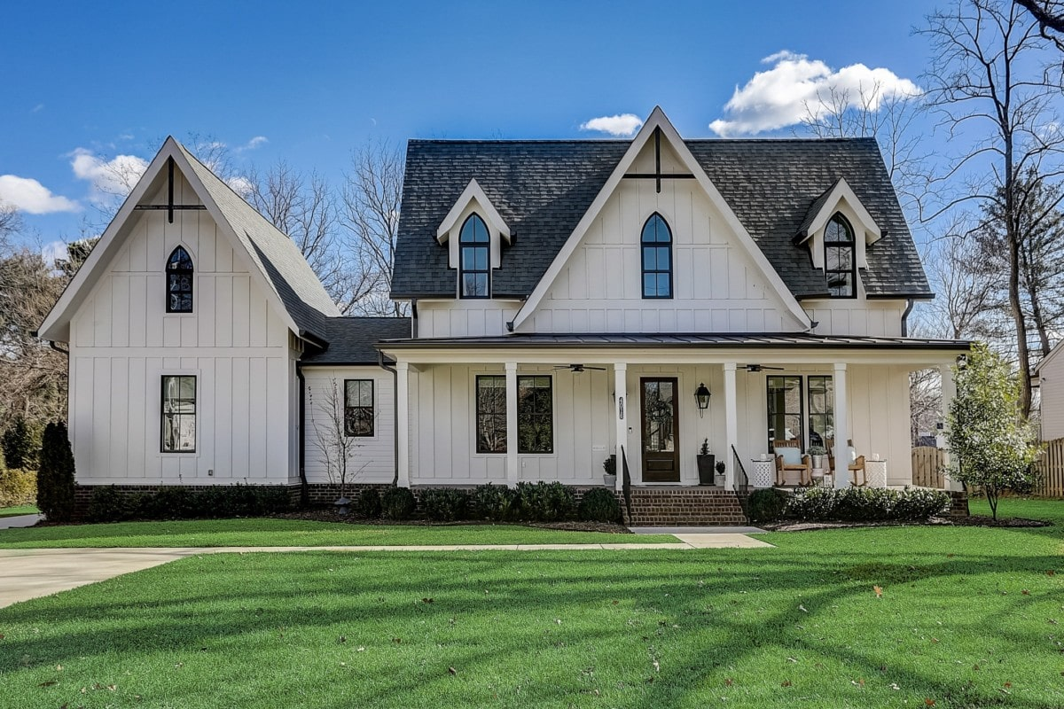 Two story white farmhouse-style home with a large lawn and black trim