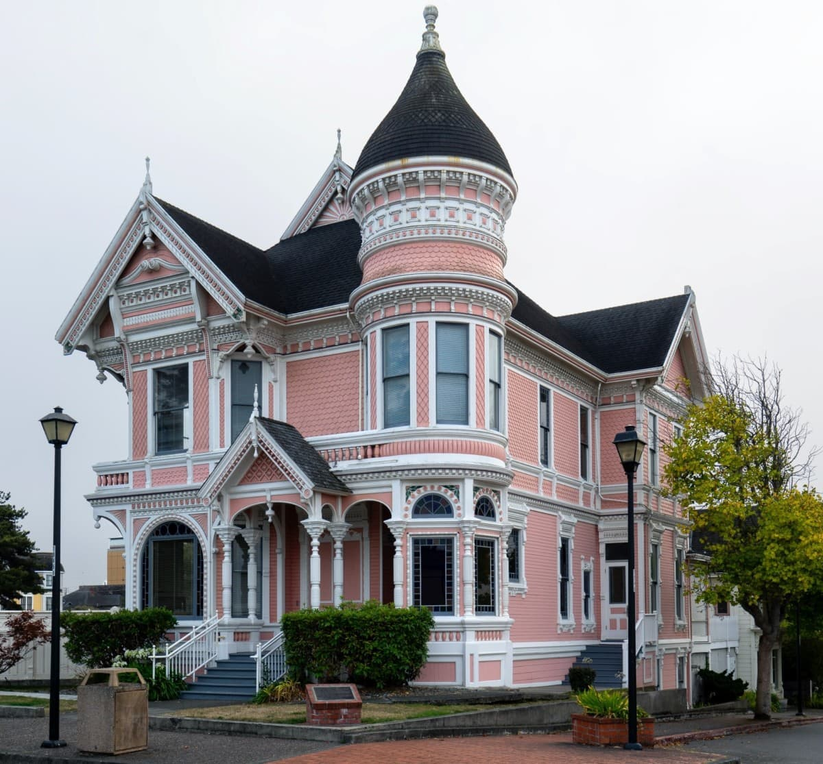 Two-story, pink victorian style home with white trim and round tower
