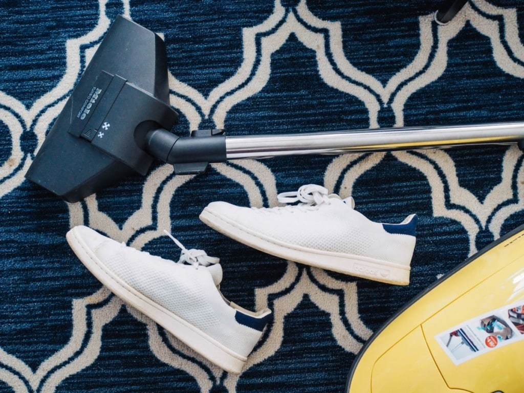 Shoes on the carpet next to a vacuum cleaning for indoor allergens