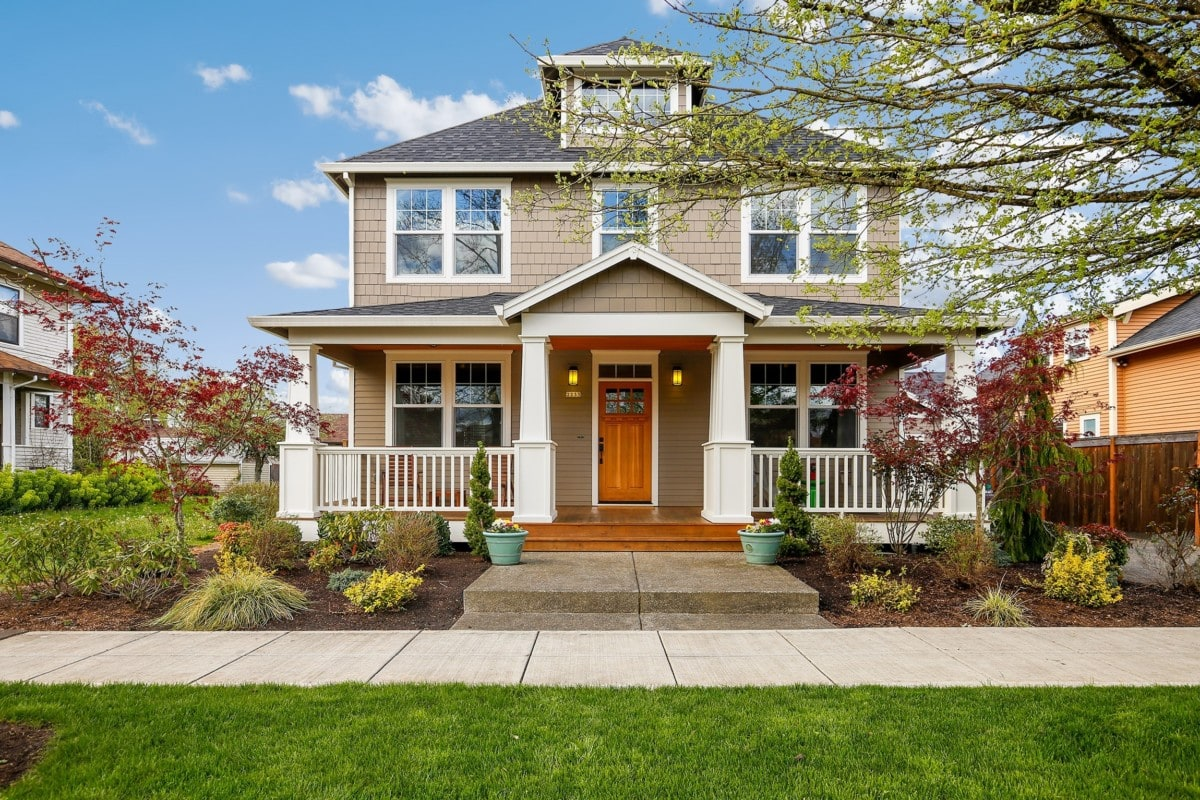 Two story home with wood door and beautiful landscaping