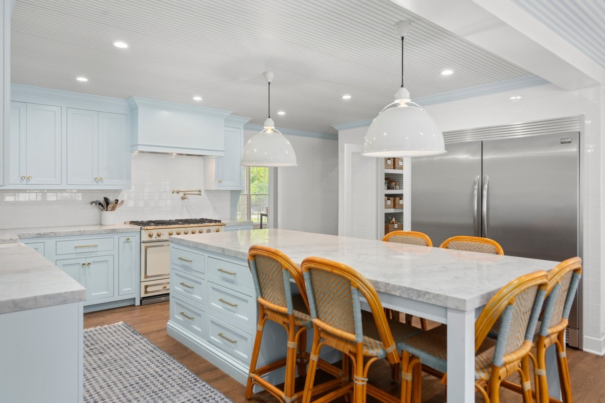 A large kitchen with gold accents and light blue cabinets